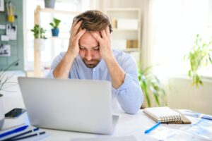 Frustrated mature businessman with laptop indoors in home office, working